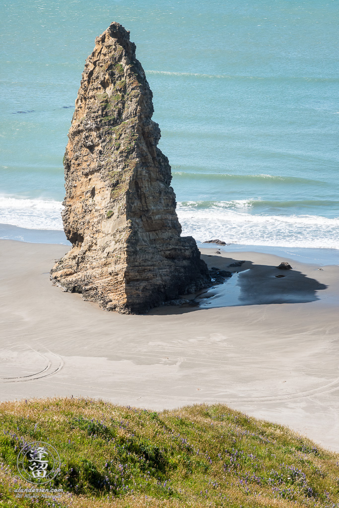 A solitary sea stack jutting up from the beach just south of the Cape Blanco Lighthouse at Cape Blanco State Park outside of Port Orford in Oregon.