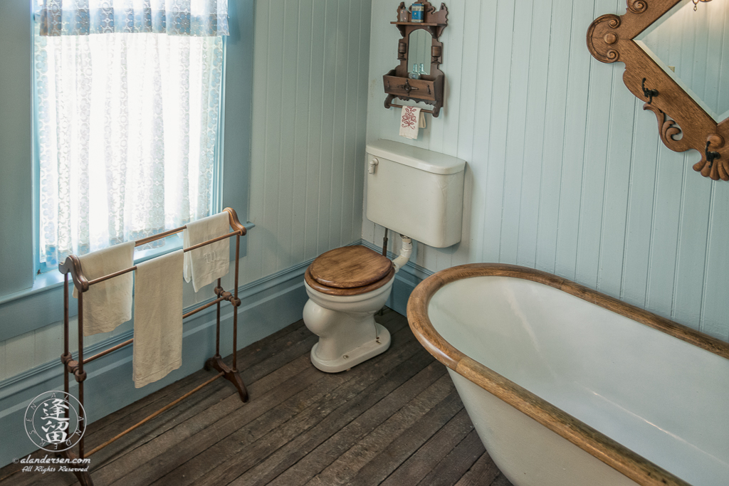 Toilet and wood-trimed claw-footed free-standing bathtub in the Master Bathroom of the Hughes House near Port Orford, Oregon.