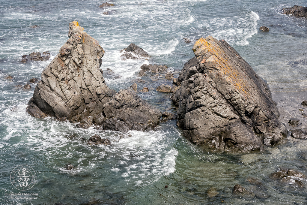 Looking down at the surf breaking on a prominent basalt rock formation from a cliff at Point St George at Crescent City in Northern California.