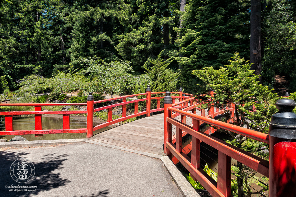 """Red Japanese """"Morning Song Bridge across Whispering Waters (creek)"""" in Choshi Gardens at Mingus Park in Coos Bay, Oregon."""