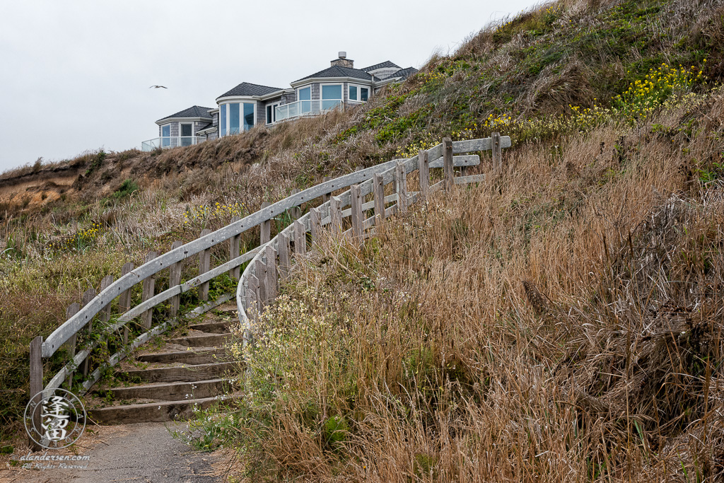 Stairs leading up to the cliff above Bandon beach, between South Jetty County Park and Coquille Point, with a private residence atop the cliff.