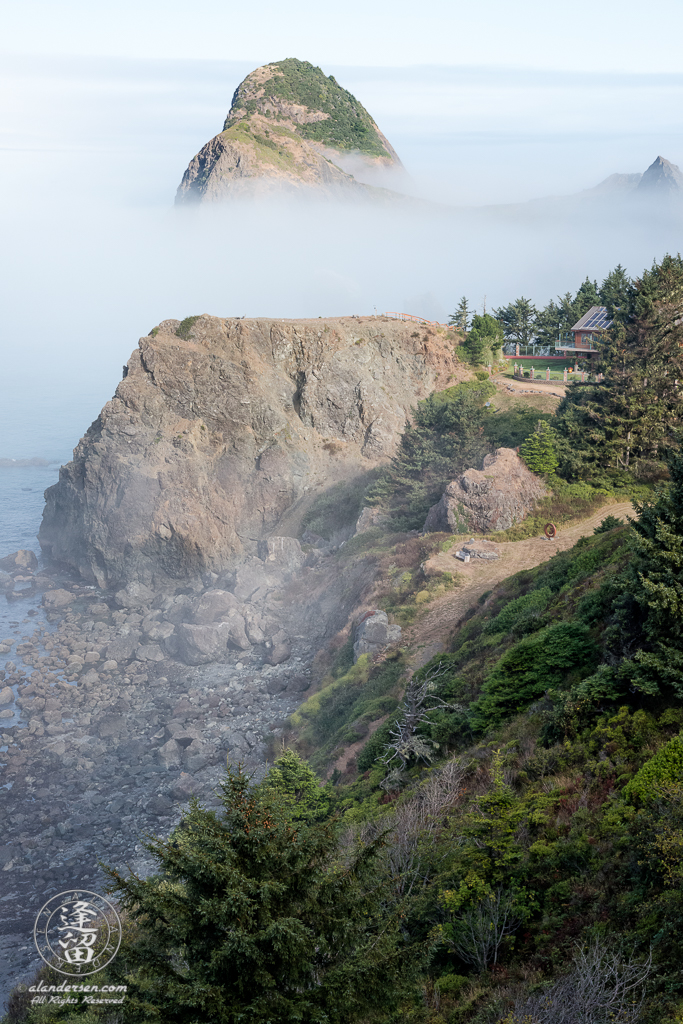 Seastacks floating in morning fog provide a fairy-tale ocean view of a cliff-side home on the Southern Oregon Coast near Ophir.